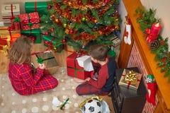 Enfants déroulant des cadeaux de Noël image stock