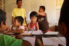 Enfants déshérités par aide avec l'éducation Photographie stock