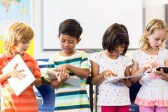 Enfants d'école à l'aide des comprimés numériques Photographie stock libre de droits