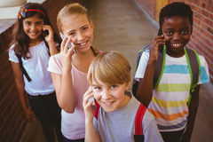 Enfants d'école à l'aide des téléphones portables dans le couloir d'école Images libres de droits