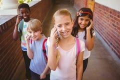 Enfants d'école à l'aide des téléphones portables dans le couloir d'école Photographie stock libre de droits
