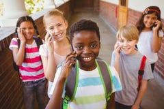 Enfants d'école à l'aide des téléphones portables dans le couloir d'école Images stock