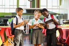 Enfants d'école à l'aide du comprimé numérique dans la cafétéria de l'école Photographie stock