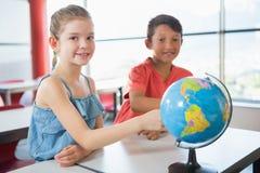 Enfants d'école étudiant le globe dans la salle de classe Images libres de droits