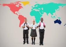 Enfants d'école devant la carte colorée du monde Photographie stock