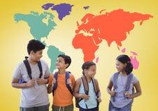 Enfants d'école devant la carte colorée du monde Image stock