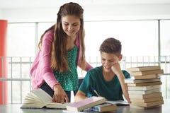 Enfants d'école faisant des devoirs dans la bibliothèque Photo libre de droits
