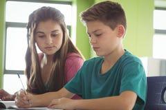 Enfants d'école faisant des devoirs dans la bibliothèque Photos libres de droits