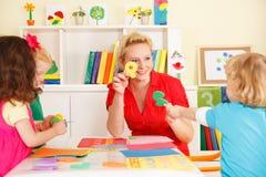 Enfants d'école maternelle dans la salle de classe avec le professeur Photographie stock libre de droits