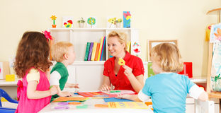 Enfants d'école maternelle dans la salle de classe avec le professeur photo stock