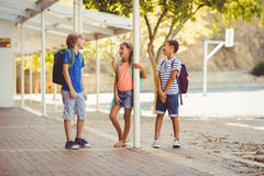 Enfants d'école parlant entre eux dans le couloir d'école Photographie stock