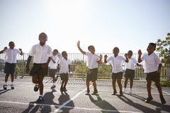 Enfants d'école primaire ayant l'amusement dans le terrain de jeu d'école Image libre de droits