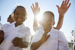 Enfants d'école primaire dans le terrain de jeu saluant l'appareil-photo Photographie stock libre de droits