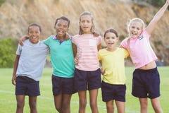 Enfants d'école se tenant avec des bras autour Photo libre de droits