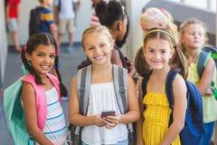 Enfants d'école se tenant dans le couloir avec le téléphone portable Photo stock