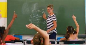 Enfants d'école soulevant la main dans la salle de classe clips vidéos