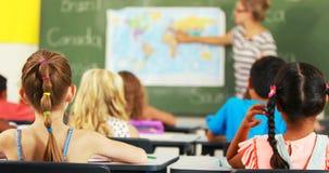 Enfants d'école soulevant la main dans la salle de classe banque de vidéos