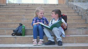 Enfants d'élèves avec des sacs à dos lisant et poussant des feuilles par un livre se reposant sur des étapes de l'école pendant l banque de vidéos