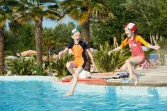Enfants d'amusement sautant dans la piscine Photo stock