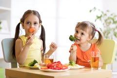 Enfants d'enfants mangeant des légumes dans le jardin d'enfants ou à la maison Image libre de droits