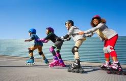 Enfants dans des casques de sécurité faisant du roller sur la voie Photo stock