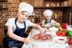 Enfants dans des chapeaux de chef faisant la pizza Photo stock