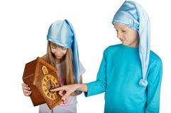 Enfants dans des chapeaux de sommeil avec l'horloge d'isolement sur le blanc Photographie stock