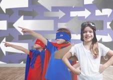 Enfants dans des costumes dans la chambre vide avec des flèches Photographie stock libre de droits