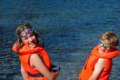Enfants dans des gilets de sauvetage par la mer Photo libre de droits