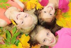 Enfants dans des lames d'automne Photographie stock libre de droits