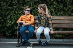 Enfants dans des lunettes de soleil parlant tout en se reposant sur le banc au parc Photos stock