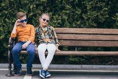 Enfants dans des lunettes de soleil se reposant ensemble sur le banc au parc Photos libres de droits