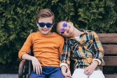 Enfants dans des lunettes de soleil tenant des mains tout en se reposant sur le banc au parc Images stock