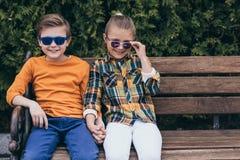 Enfants dans des lunettes de soleil tenant des mains tout en se reposant sur le banc au parc Photos libres de droits