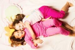 Enfants dans des pyjamas roses ayant l'amusement Enfants avec les visages de sourire images stock