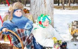 Enfants dans l'écharpe russe de pavloposadskie sur la tête avec l'impression florale sur la neige Photographie stock libre de droits