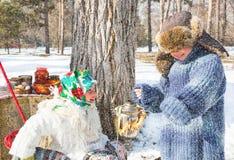 Enfants dans l'écharpe russe de pavloposadskie sur la tête avec l'impression florale sur la neige Image libre de droits