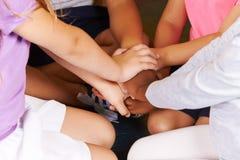 Enfants dans l'école maternelle empilant leurs mains photos stock