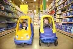 Enfants dans l'automobile de jouet Photo stock