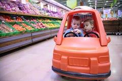 Enfants dans l'automobile de jouet Photos stock