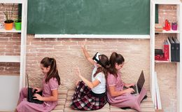 Enfants dans l'espace d'école avec des instruments se reposant sur le plancher Éducation, école moderne, étude, technologie et photographie stock
