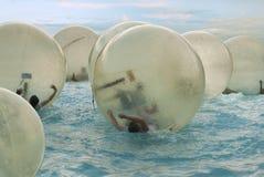 Enfants dans la boule zorbing sur l'eau photographie stock libre de droits