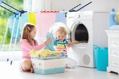 Enfants dans la buanderie avec la machine à laver photographie stock libre de droits