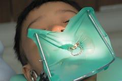 Enfants dans la chaise du ` s de dentiste dents de perçage de docteur de dentiste un garçon photos stock
