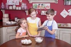 Enfants dans la cuisine essayant d'apprendre la cuisson Images stock