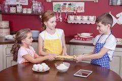 Enfants dans la cuisine essayant d'apprendre la cuisson Photo stock