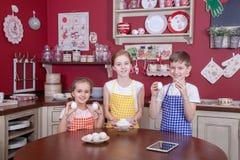 Enfants dans la cuisine essayant d'apprendre la cuisson Photographie stock libre de droits