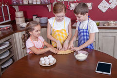 Enfants dans la cuisine essayant d'apprendre la cuisson Image libre de droits