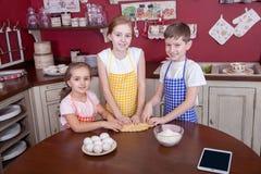 Enfants dans la cuisine essayant d'apprendre la cuisson Image stock