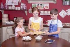 Enfants dans la cuisine essayant d'apprendre la cuisson Photos stock